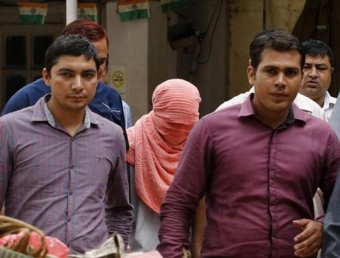 Plainclothes policemen escort an Indian teenager after he was sentenced at a juvenile court in New Delhi